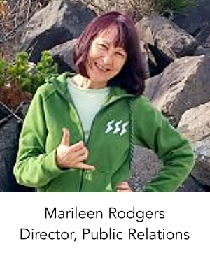 Photo of our Director of Public Relations, Marileen Rodgers. She is wearing a green flannel jacket with a t-shirt. She is at the beach, with rocks behind her. She is doing a Shaka sign with her right hand.
